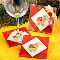 """These lavish elephant design coasters for wedding favors are in red for prosperity and feature the Indian savik link design for good luck. With good fortune on your side, we�re sure that you and your guests will have a memorable and lucky day.Each package contains 2 coasters.  The coasters measure 3.5"""" square and have rubber feet for non-slip grip.  The frame border is a traditional rich red color, enhanced with an Indian �svati� link pattern, in the center of this pattern is an elephant in…"""