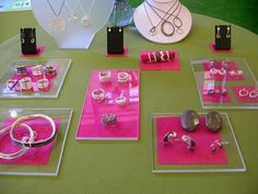 Pink fabric is strategically placed beneath rectangles of plexiglass on this jewelry display table at Craftland Shop in Providence, RI.