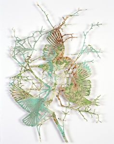 """Maps and paper cutting art come together in this series from London-based artist Claire Brewster, who says """"Nature is ever present, even in the most urban environments, taking over wherever we neglect, living in a separate yet parallel universe. I take inspiration from the natural environment, creating entomological installations of flora and fauna from imagined locations."""""""