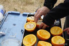 cinnamon rolls cooked in oranges over campfire