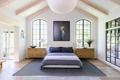 master bedroom perfection - large sclae rug over wood floors anchors the king size bed with two large scale bedside tables with wood finish and open windows