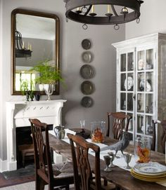 New oak-and-rush chairs surround an antique Belgian dining table in this Georgia home, all from Stanton Home Furnishings. To fashion the wall display, the owner liberated a few pewter plates from the china cabinet, made of reclaimed wood. The cast-iron pheasant was an eBay purchase.