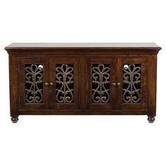 """Scrolling ironwork on 4 doors give this media console a timeless touch. Hand-finished in cinnamon brown, this regal design is a stylish setting for your flatscreen television and other essentials.    Product: Media consoleConstruction Material: Kikor woodColor: Cinnamon brown Features:  Can fit up to 65"""" TVFour doorsOpenwork designFixed shelvingHand-finished Dimensions: 32"""" H x 65"""" W x 20"""" DCleaning and Care: Do not use harsh chemicals"""
