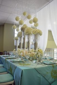 Tall floers in crystal vases & below blooms scatterd about. Now, look up for an element of surprise to find spheres of flowers dripping from the ceiling. This look would also be amazing in a mixture of color schemes but the all white adds an elegant touch.