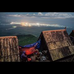 Photo by @michaelchristopherbrown. Camp view of the border cities of Goma (D.R. Congo) and Gisenyi (Rwanda) from the summit of Mount Nyiragongo an active volcano located in Virunga National Park. Visible between the camp and the two cities is half a caldera which was active in the 2002 Nyiragongo eruption. Directly behind and below the photographer who is standing on the rim of the Nyiragongo caldera is the largest lava lake in the world. Since 1882 Nyiragongo has erupted at least 34 times…