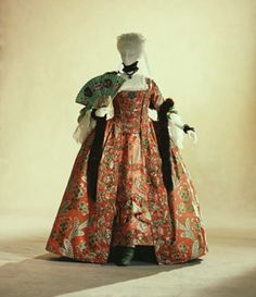 Robe a la Francaise, c. 1760  France  This is a typical Rococo period women's dress.  The ensemble shown here consists of a gown, the petticoat, and a stomacher made in a triangular panel shape. The gown opens in the front, and has large pleats folded up at the back. All this would be worn after formed with a corset and pannier, which acted as underclothes. Until clothing accepted drastic changes with the 1789 French Revolution, rich outfits, such as is shown here, ...