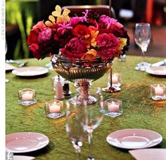Orange and moss gold-embossed table linens were an extension of the vibrant color theme. Centerpieces were arranged in antique silver urns surrounded by luminous votives.