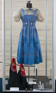 """June 4, 2011 - Beverly Hills, California, United States: Judy Garland's """"Dorothy Gale"""" original blue cotton test dress with polka dot trim and ivory sheer puff sleeve blouse from the first 2 weeks of filming and Arabian pattern test """"Ruby Slipper"""" from The Wizard of Oz, at the stunning collection of Hollywood's most iconic costumes owned by actress, Debbie Reynolds. Items will be on display for public viewing and auctioned off at """"Debbie Reynolds The Auction"""", which will be held June 18, at…"""