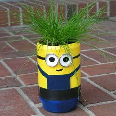 "The Minion - This popular character is easy to create from a peanut butter jar. Spray paint the bottom of the jar blue, tape a line to avoid color mixing, then paint the top portion yellow. Add details with acrylic paint. The glasses are split rings and the plant is called a ""live wire."""
