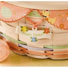 """This ceramic ivory banner style tie-on reads Happy Easter and is highlighted by peach, pastel blue and yellow flowers and has a coordinating peach ribbon included to attach to your Easter Basket or any basket. 2 1/2""""l x 1/2""""w x 2""""h."""