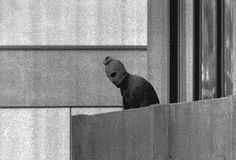 Image of hostage taker looking over the balcony of the Israeli team quarters at Building 31 of the Munich Olympic Village. This is probably the most widely recognizable and iconic photo of the event.