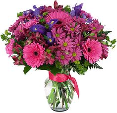 Such a breathtaking bouquet with bright pink flowers and a touch of blue iris - http://bit.ly/1FMgn9m