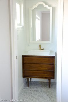 A tiny bathroom gets a remodel using a Mid-century Modern cabinet for a vanity.  White herringbone tile, octagon carrera marble flooring and champagne bronze fixtures.