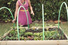 Elle fixe 4 cerceaux à son petit jardin... Son idée est vraiment BRILLANTE!!!