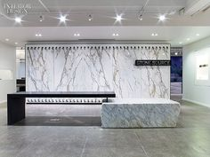 The Story of Stone: Stone Source Showroom Office by Gensler.   A block of Calacatta marble supports one end of the reception desk in stained reclaimed oak.