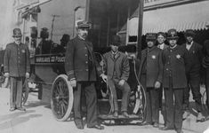 Photo of Los Angeles' first horseless patrol wagon, which also served as an ambulance. It was bought in 1904, was driven by electricity and boasted 20 miles per hour. At right is George Home, who became Chief of Police in later days. Captain C. L. Johnson is second from left. Photo dated: June 27, 1927.