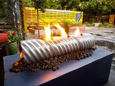 Fire Pit Design Ideas: This unique gas-powered fire feature sits atop a slab of concrete. The gas line was run through the corrugated metal pipe and covered with lava rocks. This whole backyard was done with recycled and industrial materials  the raised garden bed and privacy fence were upcycled from old shipping pallets. From DIYnetwork.com