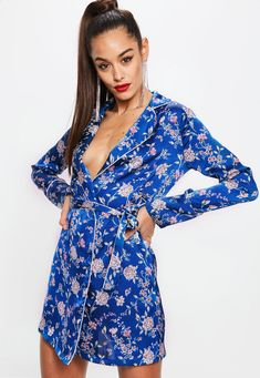 Satin mini dress featuring in a blue hue, with all over floral pattern, belted wrap front design and long sleeves.