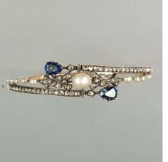 ~A late 19th century pearl, diamond and sapphire hinged bangle, circa 1890~