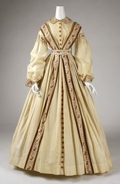 1860-65, peignoir [wrapper], American. The Met, C.I.60.11.1. [I love the lines of this one, with the angled strips of trim instead of the more common up-and-down strips on the center front. Also the bands on the sleeves and wrists. This wrapper is cotton, too; I hazard a guess that it has yellowed over the years.