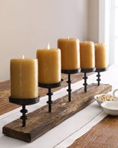 """Horchow   """"Ascan"""" Candelabra  Rustic candelabra makes an interesting centerpiece or adds extra glow to the buffet. Imported.        Handcrafted of cast iron in a natural wood base.      Clear glass candle cups (not shown).      Includes five pillar candles; may vary in color from those shown.      32""""W x 5""""D x 10""""T"""