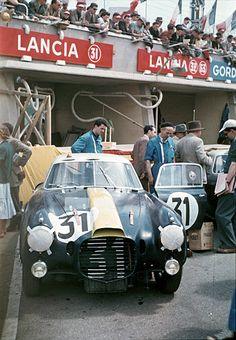 This lovely color image was taken in the pits at Le Mans before the start of the 24 Hours on June 13, 1953. This Lancia berlinetta was a D20 with supercharger, one of four entered by Scuderia Lancia that year.