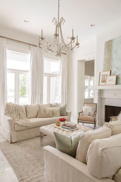 Simple lines keep the living room from feeling overly formal. Linen slipcovered sofas, reproduction French chairs and rug from The French Mix; chandelier and Austin James abstract from Rivers Spencer Interiors.