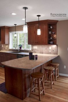 Kitchen remodel by Renovisions. Cherry cabinets, shaker cabinets, under cabinet lights, tuscan-clay-look porcelain tile backsplash, quartz countertop, peninsula, corner open shelves, pendant lights, recessed lights.
