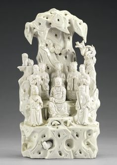 AN UNUSUAL DEHUA FIGURE GROUP OF ZHENWU AND ATTENDANTS 17TH CENTURY depicting Zhenwu seated in the center of a rocky landscape with a tortoise and serpent beneath the deity's feet, flanked by attendants and the Three Great Emperor officials and two robed attendants standing behind, the animals of the 'four directions' situated on the rocky outcrop, as well as a rabbit, bat and mythical beast Height 12 1/8  in., 30.8 cm 10/15000