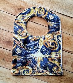 Looking for a stylish way to keep your little geek clean? Your search ends here with an adorable exploding TARDIS bib! This Doctor Who bib features the Van Gogh style painting featured in Doctor Who!  The bib is topped with 100% Cotton, backed with absorbent Terry Cloth and silver style snap fastenings. Bibs are top-stitched for durability. Pattern placement may vary.  Listing is for one bib only. Suitable for machine wash and medium-heat dryer setting.  Everything is handmade in our…