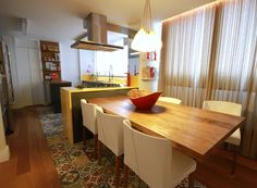 A sala de jantar foi integrada à cozinha com mesa de madeira de demolição, da Aroeira, e cadeiras orquídea de couro branco, da Dpot (Foto: Mário Bock/Divulgação)