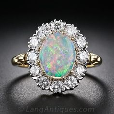 A fabulous luminous opal of many colors glows from within a sparkling halo of European-cut diamonds in this splendid classic style mounting, handcrafted in London, England to emulate a traditional Victorian-era ring. 18 karat two-tone gold, English hallmarks.