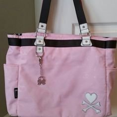 """Tokidoki large tote bag Cute, pink large tote bag. Many uses...shopping, diaper, weekender, travel bag. See last photo for few flaws. Mainly on bottom and corners. Washed it to see if it would come off but it didn't take all off.  Size: 12"""" H; 13"""" W; 5"""" D Top handles with 9.5"""" strap drop Zipperd main closure Large exterior pocket with magnetic closure 2 side pockets with magnetic closure Interior zip pocket and 2 open cellphone size pockets Nylon print fabric makes for easy cleaning…"""