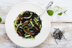 Black ink pasta with tomatoes. by kawizen  on Creative Marketpasta #blackpasta #blackinkpasta #courgette#sundriedtomatoes #tomatoes #capers #whitewoodbackground #whiteplate #onplate #silverfork #freshherbs#dinner #lunch #diningexperience #healthyeating #food #zucchini #gourmet #diet