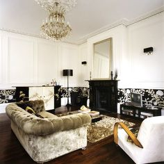 luxurious champagne velvet chesterfield sofa with a crystal chandelier, wood floor, amazing fireplace and brasserie
