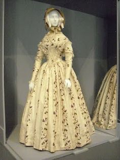 """Dress: England, 1845-49   Silk plain weave with warp-float patterning, printed, silk lace, and silk passementerie    """"By the mid-1840s, dresses with sloped shoulders, tight bodices with fitted sleeves, and fuller skirts mirrored the similarly constricting social norms of the early Victorian woman. Bodices often included rows of pleat extending over the shoulder to the waist in a pronounced V-shape that pointed to the wide, cartridge-pleated skirt."""""""