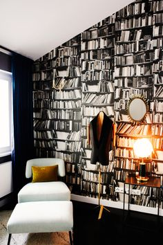 Office with bookcase printed wall paper and white furniture