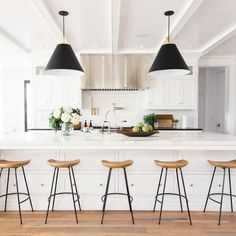 black pendents, black and wood stools, wooden floor, large extractor hood, white work top