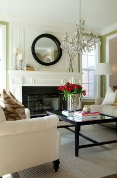 living rooms - white tufted sofa black glass-top rectangular coffee table green walls white fireplace black tiles faux bamboo chandelier black convex mirror