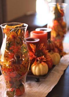 décoration de table automne - vase en verre rempli de feuilles d'automne et arrangement de citrouilles, bougies cylindriques et fleurs artificielles
