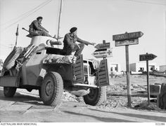 DERNA, LIBYA. 1941-12. MEMBERS OF THE CREW OF AN ARMOURED FIGHTING VEHICLE PONDER OVER THE GERMAN AND ITALIAN ROAD SIGNS.