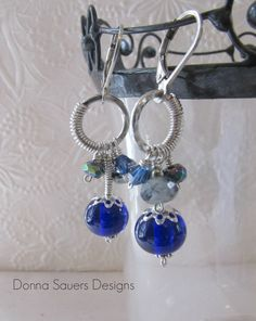 Rich cobalt blue earrings in a unique circle design with handmade glass beads. Cobalt blue glass beads are surrounded by semi precious gems including Tourmalinated Quartz and Mystic Pyrite. Donna Sauers Designs $58