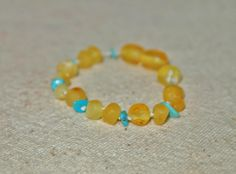 Baltic Amber Teething Bracelet—turquoise and raw (unpolished) lemon-colored baroque style beads, white cotton string, plastic screw clasp by LilSports on Etsy https://www.etsy.com/listing/251513384/baltic-amber-teething-braceletturquoise