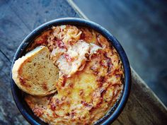 The Ultimate Crab Dip/ 1 cup cubed white bread, crusts removed (1 1⁄2 oz.) 2⁄3 cup whole milk 1 1⁄2 tsp. extra-virgin olive oil 1 tsp. fresh oregano, minced 1⁄3 cup minced yellow onion (1 3⁄4 oz.) 11 oz. king crab meat, cooked and roughly shredded (1 lb. 6 oz. in shells) 2 tbsp. heavy cream Kosher salt and freshly ground black pepper to taste 1⁄3 cup grated Grana Padano cheese (1⁄2 oz.) 8 slices toasted country bread