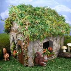 Two tiny squirrels enjoy our squirrel themed fairy house in our miniature fairy garden.