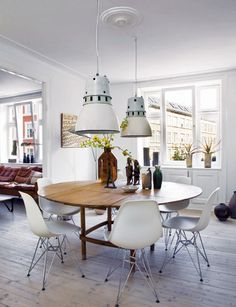 Contrast -- sleek white Eames chairs with warm, earthy wooden table