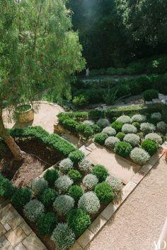 Green dwarf myrtle and gray westringia rosmariniformis are planted in a checkerboard pattern on the south terrace of Villa Corbeau in Santa Barbara, California | archdigest.com