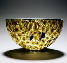 Roman dish:    This Roman dish is made of 'millefiori glass', a kind of mosaic glass. The technique used gives the impression of a bouquet with a thousand flowers. The dish has been part of a luxury tableware and was used for serving snacks such as olives or dates. It is pressed into a mold and made up of interconnecting molten glass fragments, ca. 0-100 A.D.