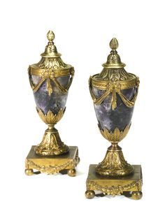 A pair of George III blue john and gilt-metal cassolettes in the manner of Matthew Boulton, the reversible lids with a leaf-cast finial and foliage, the baluster drip-pan ornamented with foliage and with fluted decoration, the ovoid blue john body ornamented with swags, on a leaf- cast socle and square base with floral garlands, on ball feet