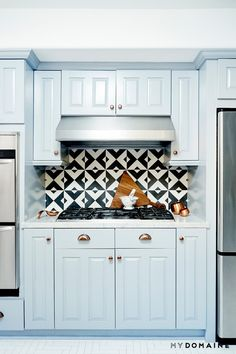 A kitchen with herringbone white floors, and baby blue cabintets with brass and copper hardware